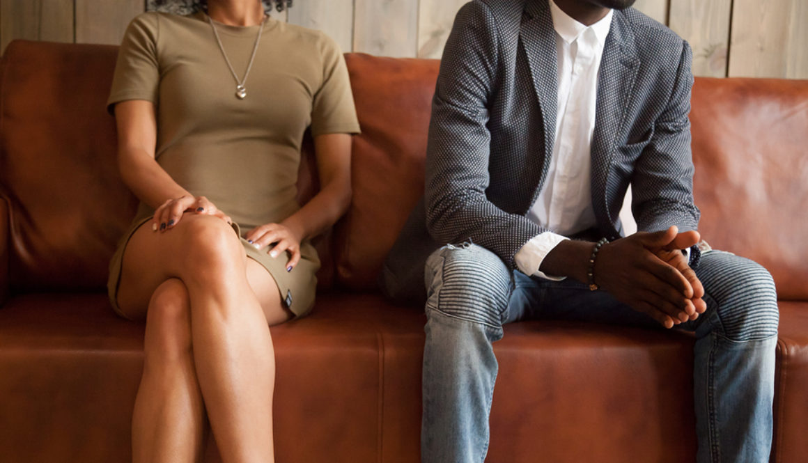 African american unhappy couple sitting on couch after quarrel fight thinking of break up or divorce, black upset man and woman not talking having conflict, bad relationships concept, close up vie